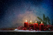red advent candles burning, dark snowy background with copy space