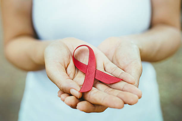 red aids ribbon in hand. red aids ribbon in hand. soft focus on ribbon hiv stock pictures, royalty-free photos & images