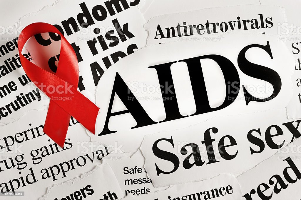 Red AIDS ribbon on headlines concerning the disease stock photo