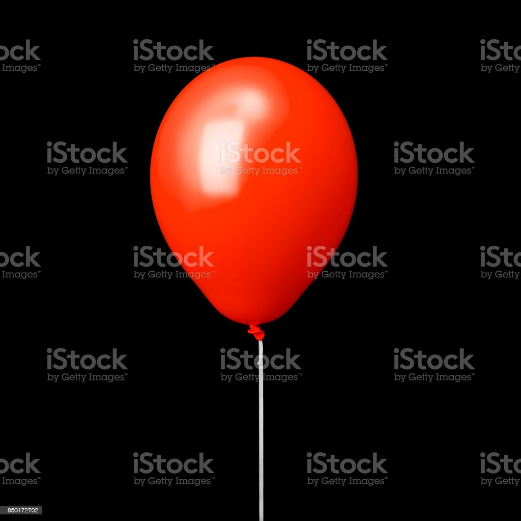 Red air balloon on white ribbon isolated on black stock photo