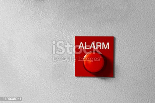 Red Alarm button signal on the painted grey wall. Concept of any alarm situation - fire, bankrupt, robbery etc.