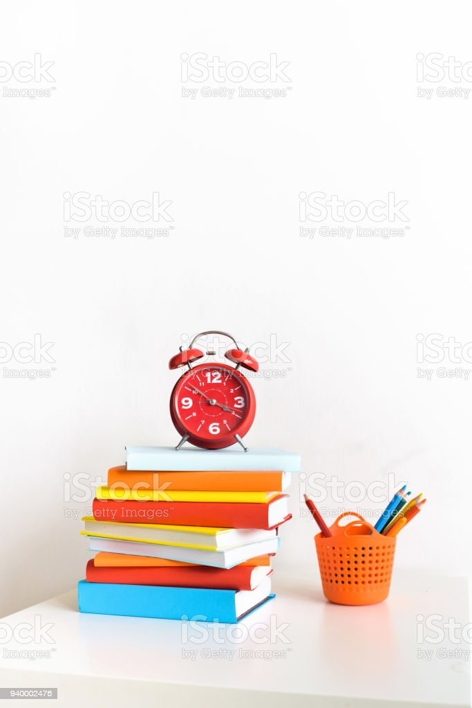 Red alarm clock and colorful books stock photo
