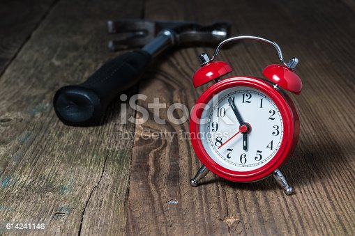 istock Red alarm clock and hammer on the wooden table 614241146