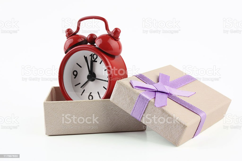 Red alarm clock in a cream box with lilac ribbon stock photo