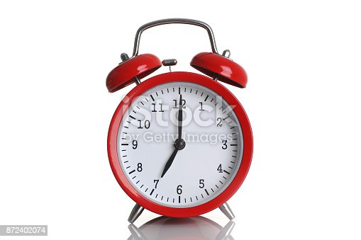 Red alarm clock isolated on white background shows seven o clock in the morning time to get up to wake up and have breakfast morning or evening run to go to work 7 am pm.