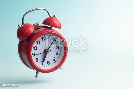 Red alarm clock on blue