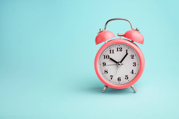 Red alarm clock on blue background stock photo