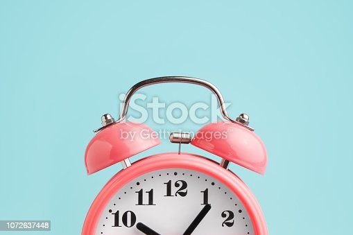 istock Red alarm clock on blue background 1072637448