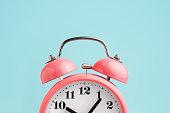 istock Red alarm clock on blue background 1072637448