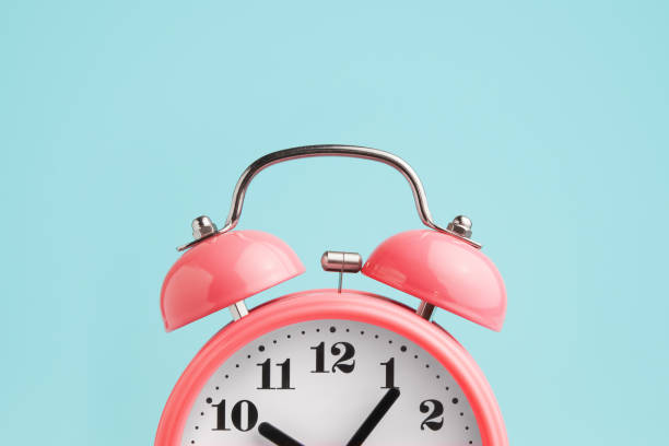 red alarm clock on blue background - alarm stock pictures, royalty-free photos & images