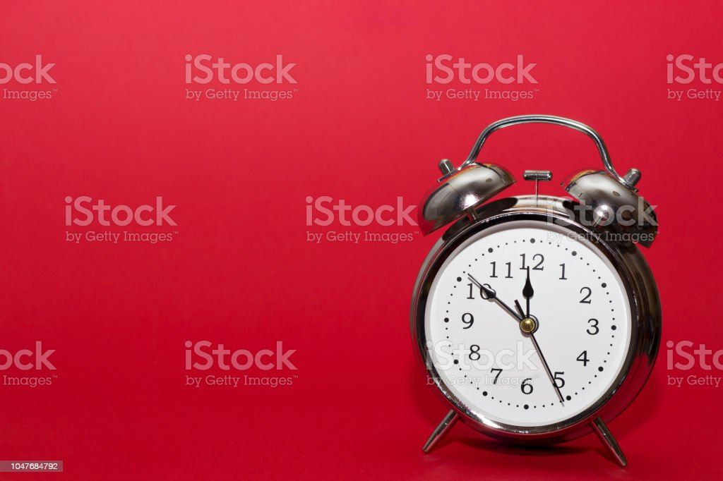 red alarm clock on red background. close up shot. top view. stock photo