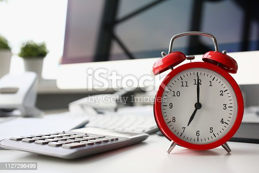 Red alarm clock set at eight in the morning closeup standing on office table. Business or education 7 o'clock management concept