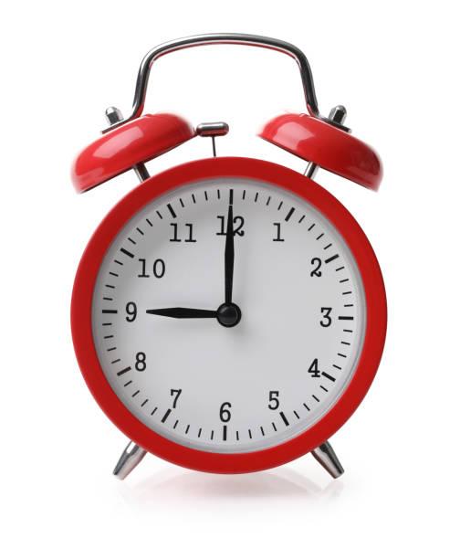 Red alarm clock set at nine isolaten over white background stock photo
