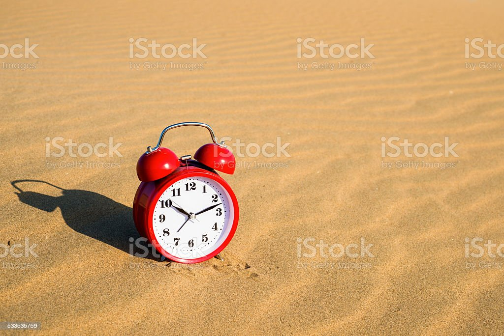 Red alarm clock   sitting on the sand with water stock photo