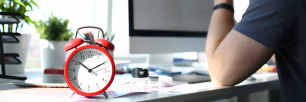 Red alarm clock stand at worktable with thoughtful man Red alarm clock stand at worktable with thoughtful man in background closeup information sign stock pictures, royalty-free photos & images