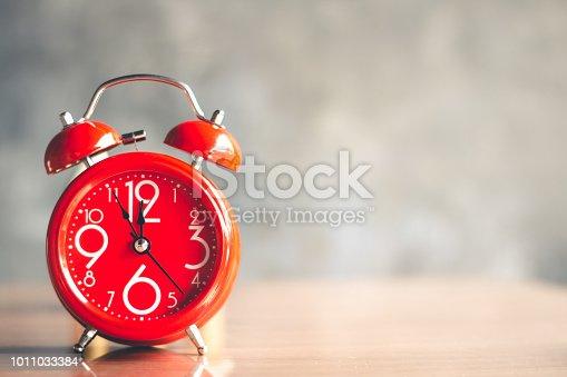 istock Red alarm clock with five minutes to twelve o'clock, retro clock. 1011033384
