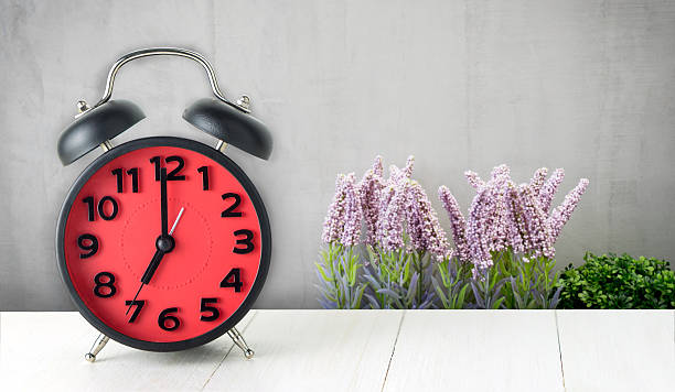 red alarm clock with flower background - attaquant photos et images de collection