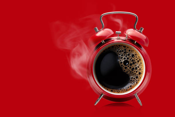 Red alarm clock with hot black coffee. Hot coffee in a retro alarm clock. Wake up alarm coffee concept. morning stock pictures, royalty-free photos & images