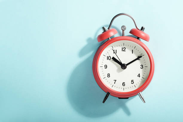 Red alarm clock with shadow lying on blue background. View from above. stock photo