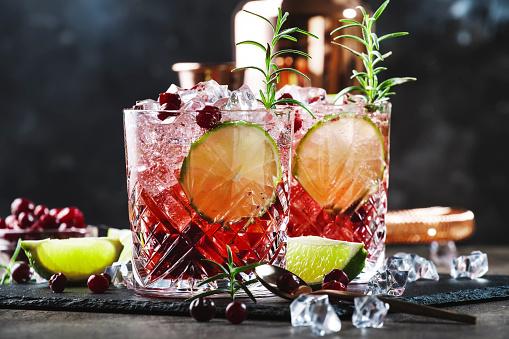 Rode Alcoholcocktail Met Veenbessen Ijs En Rozemarijn Op Houten Achtergrond Kopieerruimte Stockfoto en meer beelden van Alcohol