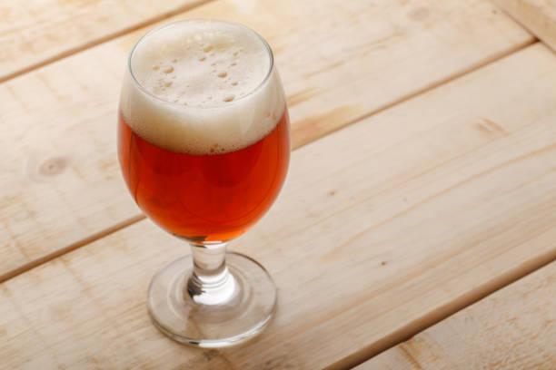 cerveja vermelha em madeira clara - ale - fotografias e filmes do acervo