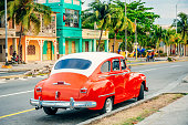 Red American car parking at a street of Cienfuegos, Cuba