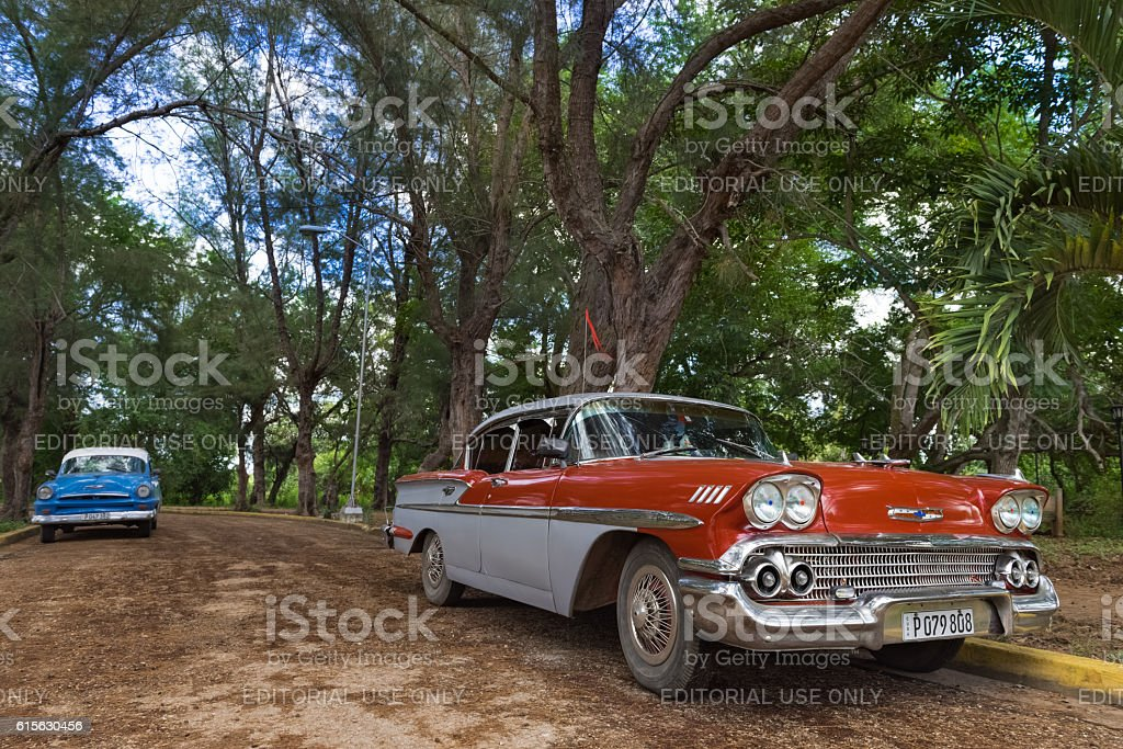 Red american Chevrolet parked under palms in Santa Clara Cuba stock photo