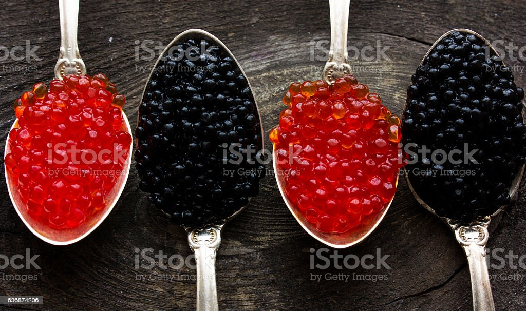 Red and Black caviar beads on silver spoon close-up stock photo