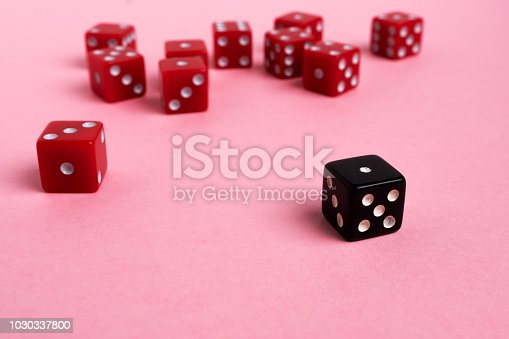 Red and black gaming dices on pink background. Game concept.