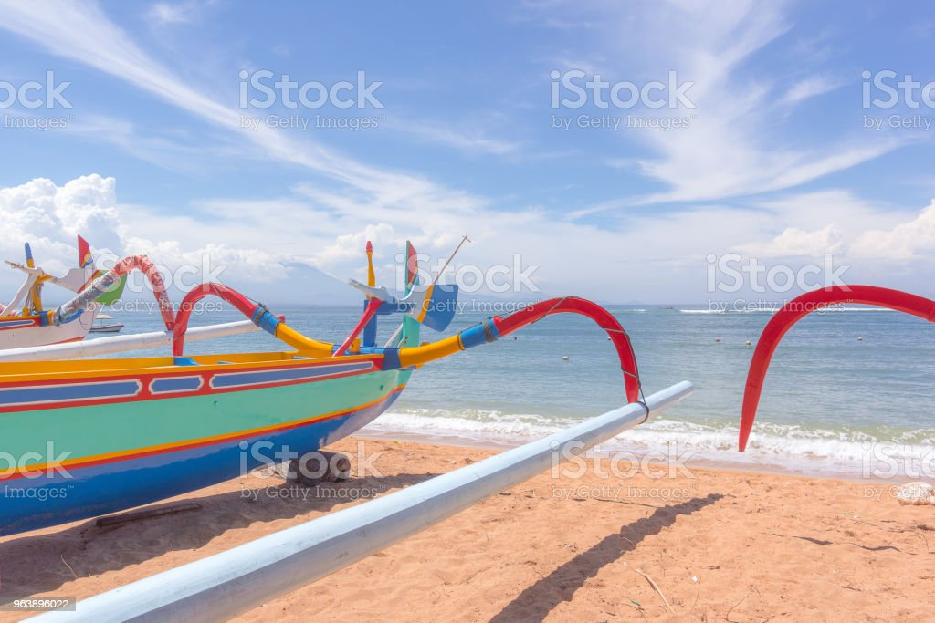 Red and blue boats on a balinese beach in front of the turquoise ocean - Royalty-free Bali Stock Photo