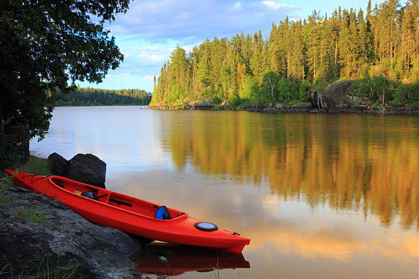 A red and blue canoe at the lake on a lovely day stock photo