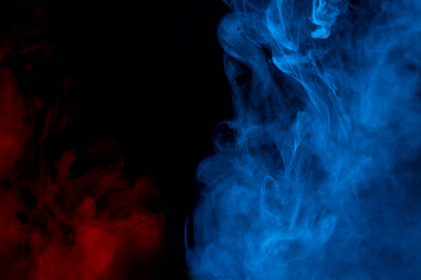 red and blue clouds of cigarette vapor colored fog on a dark background smoking concept stock photo