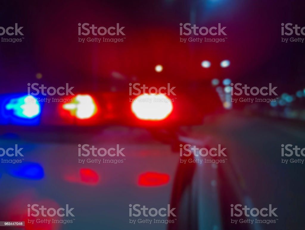 Red and blue flashing police car lights at night, crime scene. Abstract blurry image to illustrate criminal news and events. Red and blue flashing police car lights at night, crime scene. Abstract blurry image to illustrate criminal news and events. A Helping Hand Stock Photo