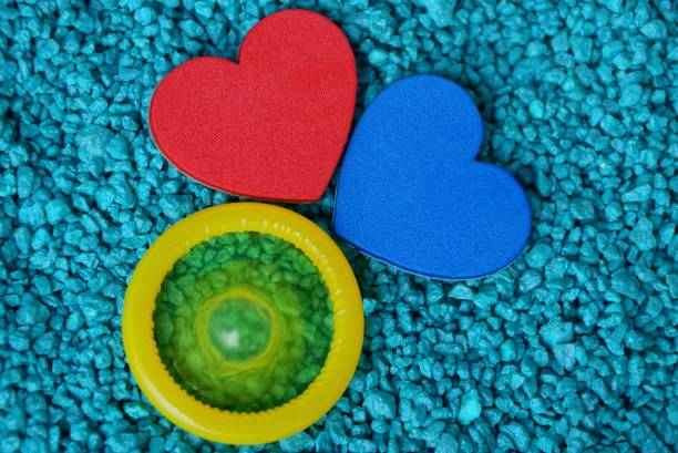 red and blue heart and yellow condom on small stones red and blue heart and yellow condom on small blue stones sexually transmitted disease stock pictures, royalty-free photos & images