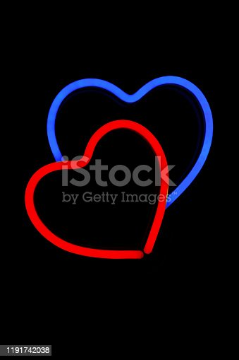 90822324 istock photo Red and blue heart in one neon sign on isolated black background. 1191742038