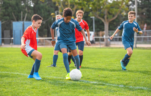Red and Blue Jersey Boy Footballers Competing on Field stock photo