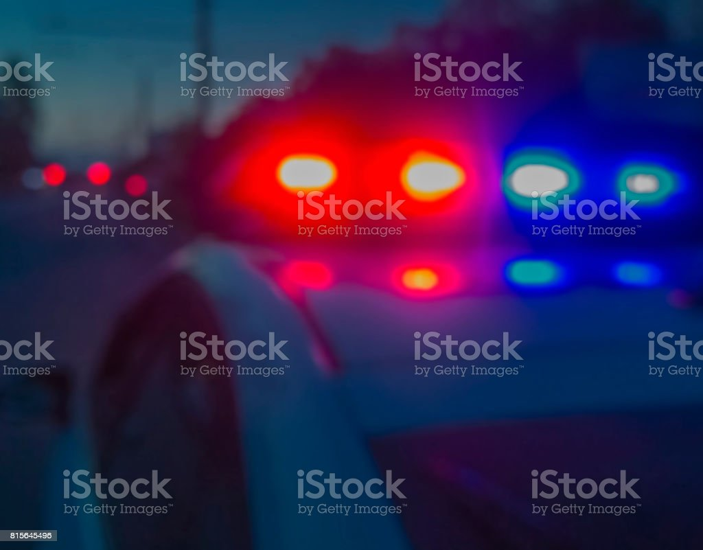 Red and blue lights of police car in night time, crime scene. Night patrolling the city. Abstract blurry image. stock photo