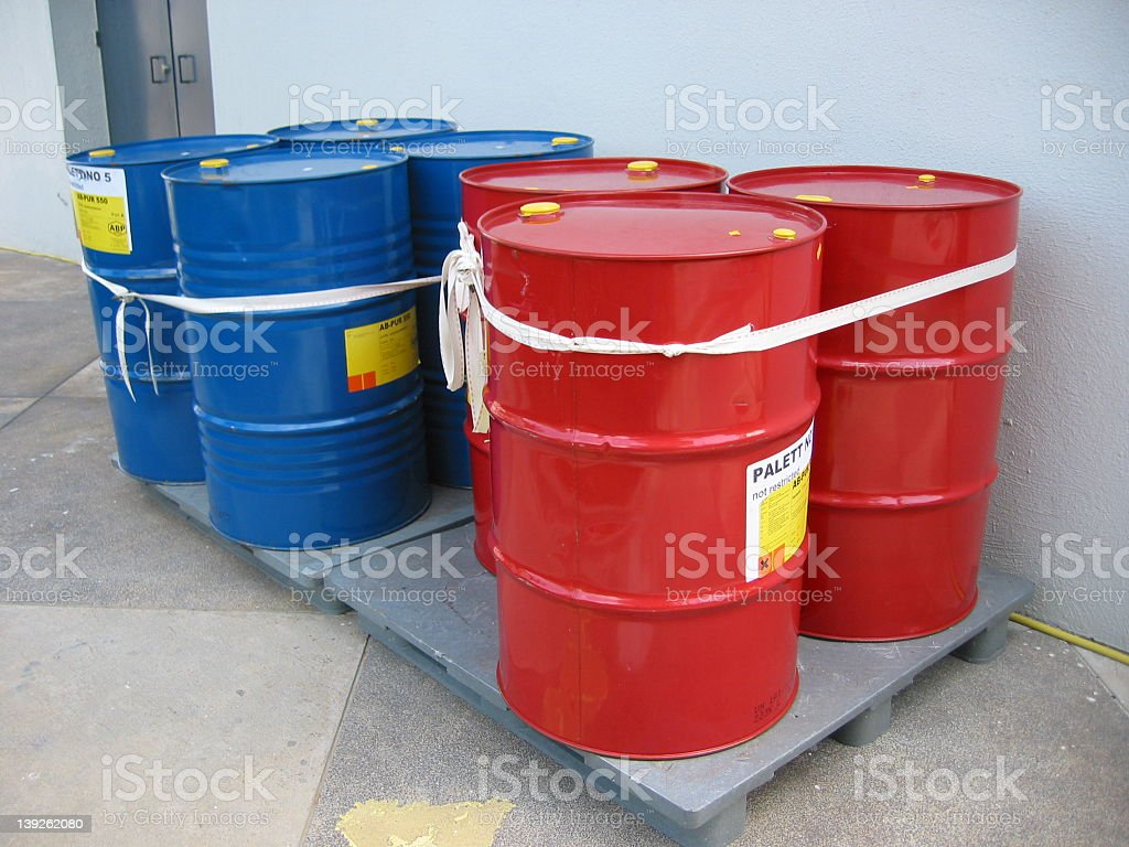 Red and blue metal barrels for holding various liquids stock photo