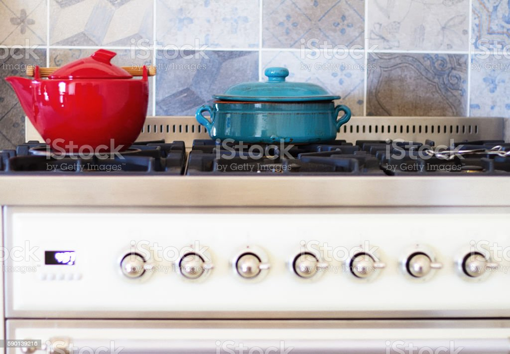 Red and Blue Pots on Pretty Vintage-Style Kitchen Stove stock photo