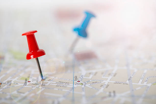 red and blue push pin stuck in a street map - épingle photos et images de collection