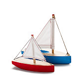 Red and blue toy sailboats, isolated on white.