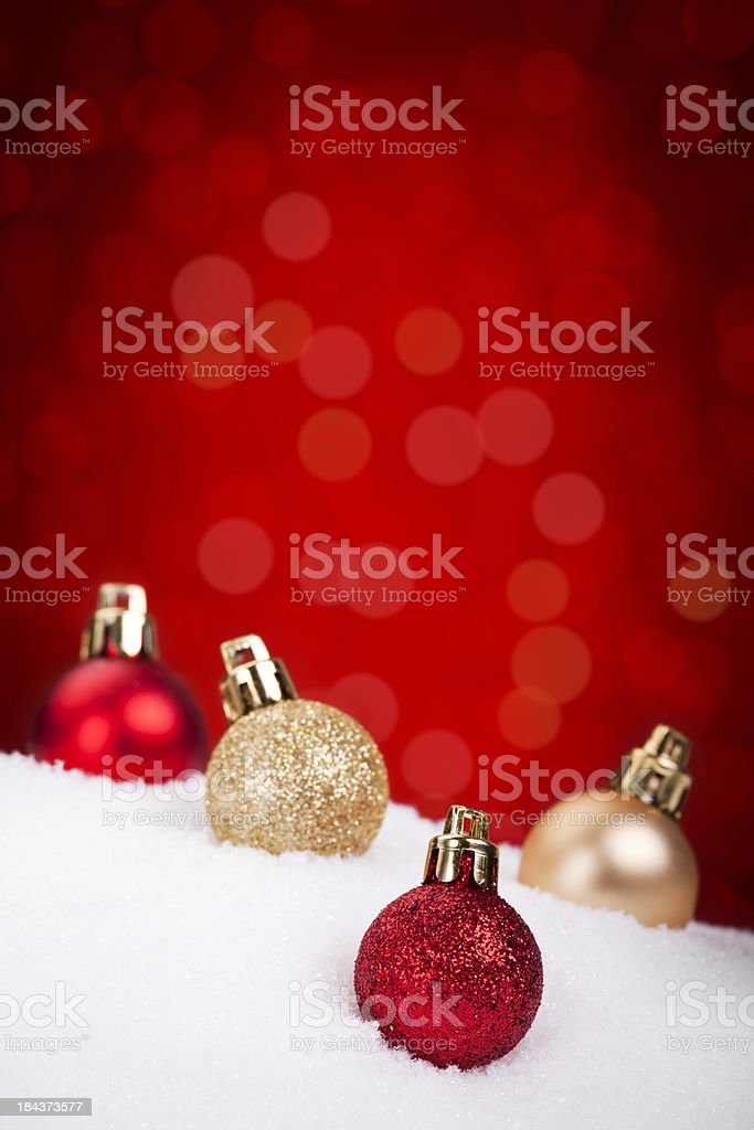 Red and gold Christmas baubles on snow, red background royalty-free stock photo