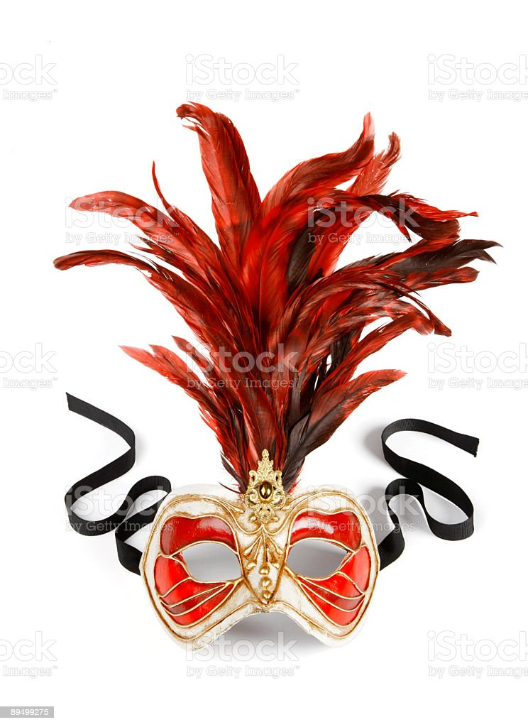 A red and gold mask with large, elaborate red feathers royaltyfri bildbanksbilder