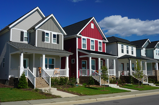 Street view of a row of houses.  The front of each house has a porch, stairs and a sidewalk.
