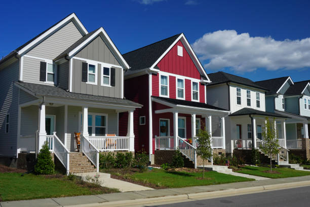 Red and Gray Row Houses in Suburbia Street view of a row of houses.  The front of each house has a porch, stairs and a sidewalk. residential district stock pictures, royalty-free photos & images