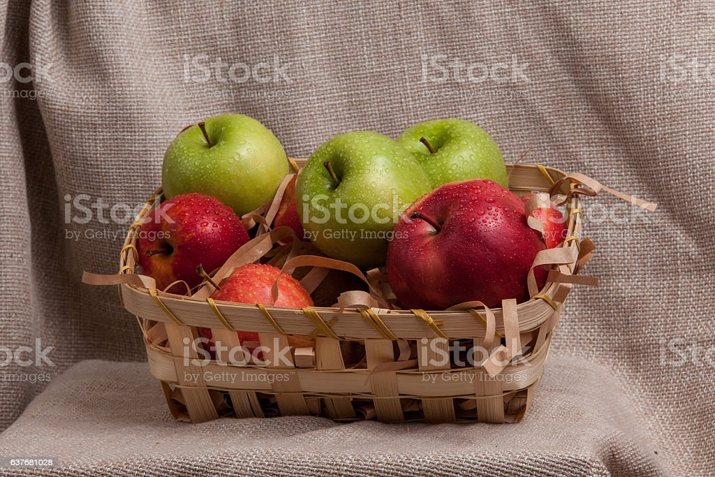 red and green apples in a basket stock photo