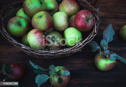 1020586746istockphoto Red and green apples in basket on wooden table 1036562268