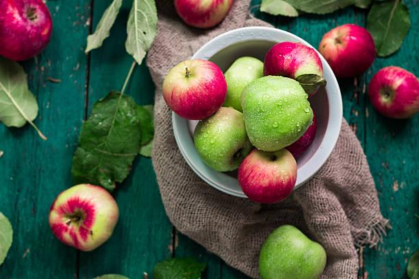 red and green apples on wooden vintage background - tropfenblatt tisch stock-fotos und bilder