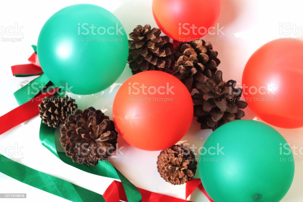 red and green balloons, ribbon and pine cones stock photo