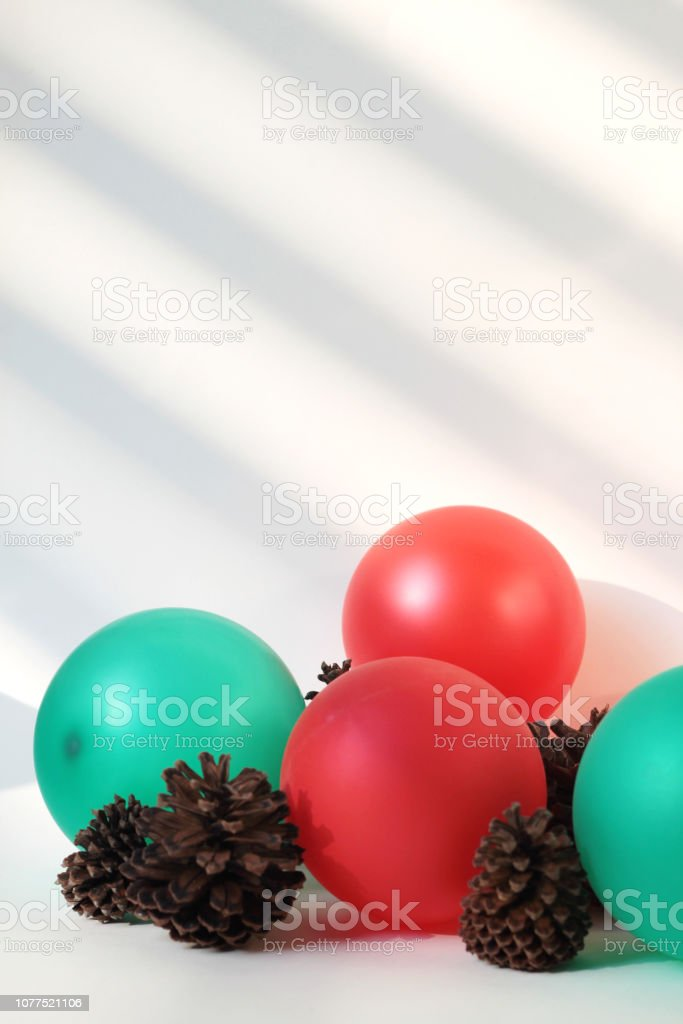 red and green balloons with dried pine cones stock photo